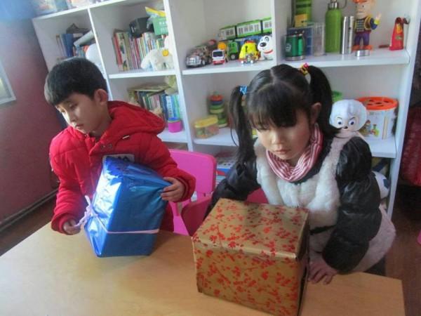 Caleb on left opening present